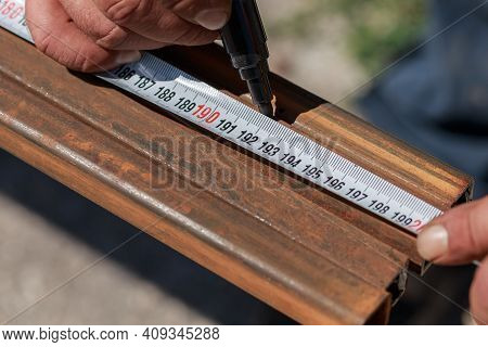 Man Master Builder Measures Metal With A Working Measuring Tool, Tape Measure And Marker In The Hand