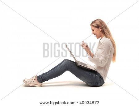Profile of a blonde girl rejoicing while is using a laptop computer