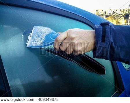 Man Scrapes Hoarfrost With A Plastic Scraper From The Side Window Of A Blue Car. Hand Without Gloves