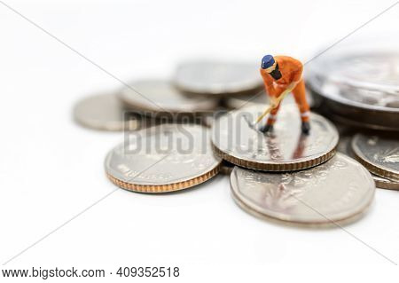 Miniature Worker Digging On Coins Stack. Concept Of Money And Investment.