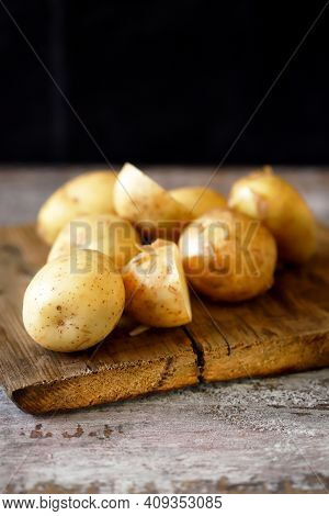 Raw Potatoes On A Wooden Surface. Potato Harvest Concept.