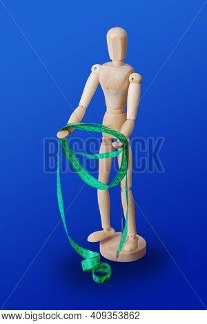 Wooden toy figure with measuring tape on blue background
