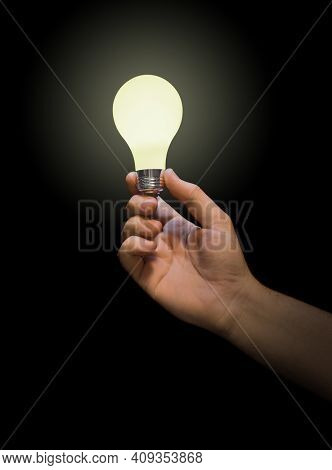 Lighting lamp in hand isolated on black background