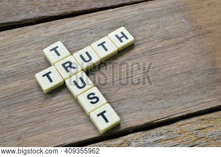 Square Letters With Text Trust And Truth Over Wooden Background.