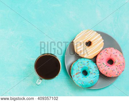 Top View Of Assorted Donuts And Coffee On Blue Concrete Background With Copy Space. Colorful Donuts