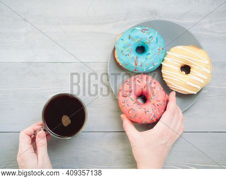 Woman Hands With Coffee And Assorted Donuts Over Gray Wooden Table. Top View Of Colorful Donuts And