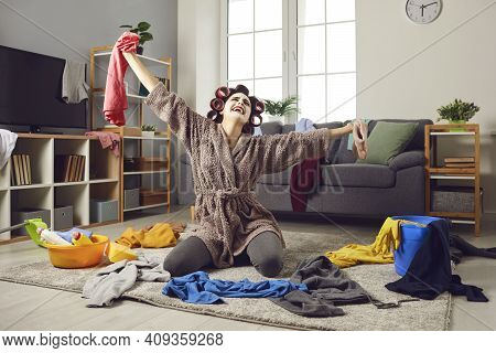 Tired Housewife Crying While Cleaning Up Mess And Picking Up Scattered Clothes From Floor