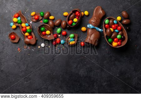 Chocolate easter eggs, choco rabbit and colorful sweets on stone background greeting card. Top view. Flat lay with space for your greetings