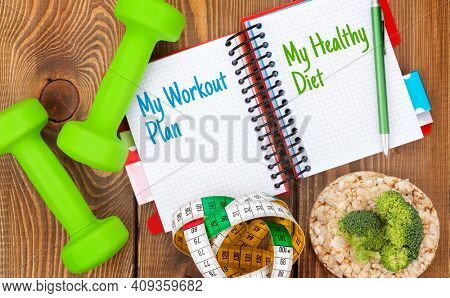 Dumbells, tape measure, healthy food and notepad for workout plan and healthy diet. Fitness and health. Top view flat lay