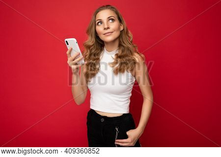 Happy Pretty Young Blonde Woman Wearing White T-shirt Isolated Over Red Background Using Smartphone