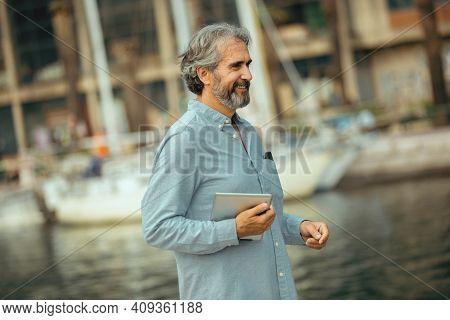 Portrait Of Retirement Handsome Senior Man Holding Tablet Computer On Seafront