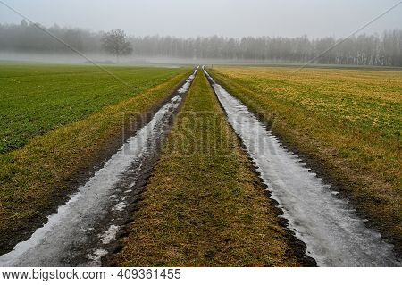 Straight Icy Road Between Agriculture Fields In Sweden