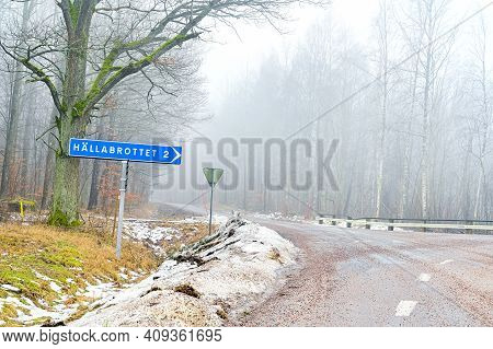 Road Crossing With Sign Showing The Way To Hallabrottet 2 Kilometers