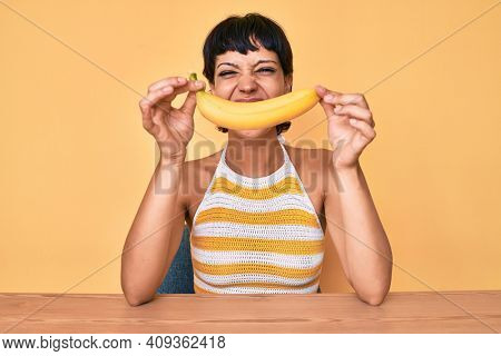 Brunette teenager girl holding banana like funny smile sticking tongue out happy with funny expression.