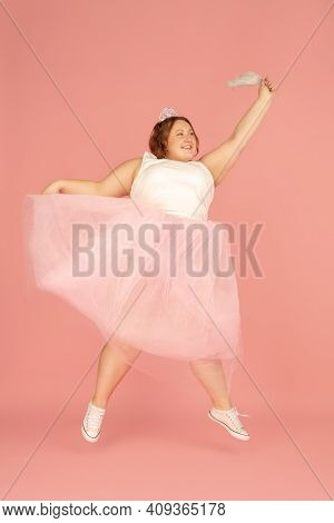 Jumping. Beautiful Plump Caucasian Plus Size Model In Fairys Outfit Isolated On Pink Studio Backgrou