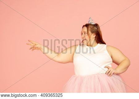 Pointing. Beautiful Plump Caucasian Plus Size Model In Fairys Outfit On Pink Studio Background. Conc