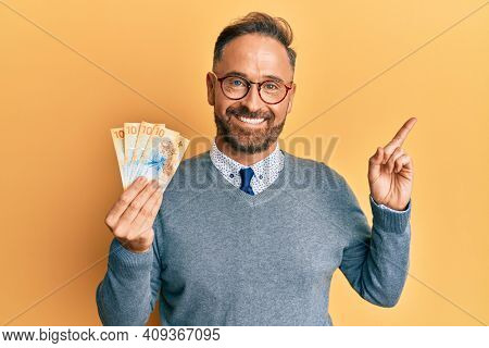 Handsome middle age man holding swiss franc banknotes smiling happy pointing with hand and finger to the side
