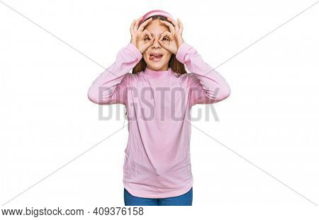Beautiful brunette little girl wearing casual turtleneck sweater doing ok gesture like binoculars sticking tongue out, eyes looking through fingers. crazy expression.
