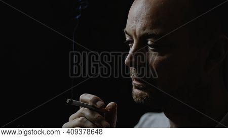Close Up Of A Young Man Smoking A Cigarette Looking Thoughtful And Stressed. Isolated On Black Backg