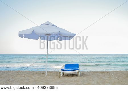 Beach Chair And Umbrella Without People During The Crisis Of The Tourism Industry. The Concept Of Th