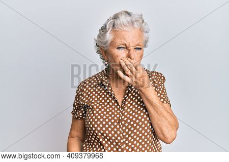 Senior grey-haired woman wearing casual clothes smelling something stinky and disgusting, intolerable smell, holding breath with fingers on nose. bad smell