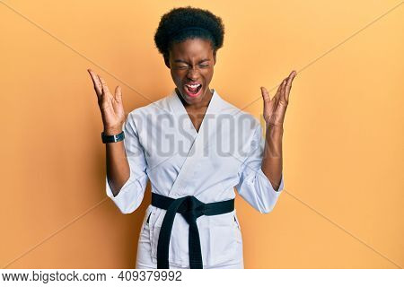Young african american girl wearing karate kimono and black belt celebrating mad and crazy for success with arms raised and closed eyes screaming excited. winner concept