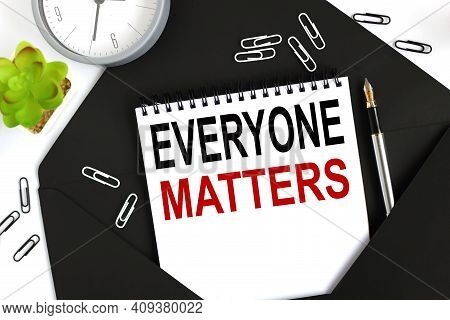 Everyone Matters. Text On A Sheet Of Notepad On A Black Envelope On A Light Background