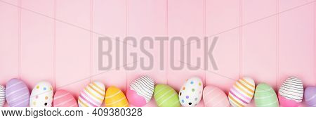 Colorful Easter Egg Bottom Border Over A Soft Pink Wood Banner Background. Top Down View With Copy S