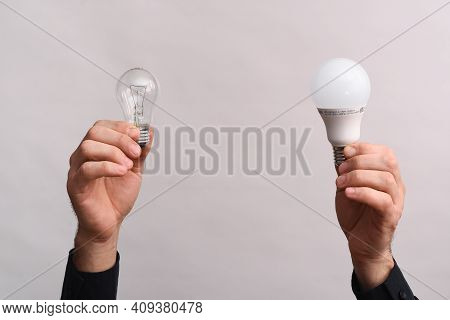 In The Male Hands, An Led Lamp And An Incandescent Light Bulb. The Concept Of Energy Saving.