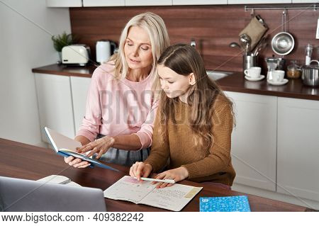 Teen Child Daughter Studying At Home In Kitchen With Mom. Teenage School Kid Girl Distance Learning