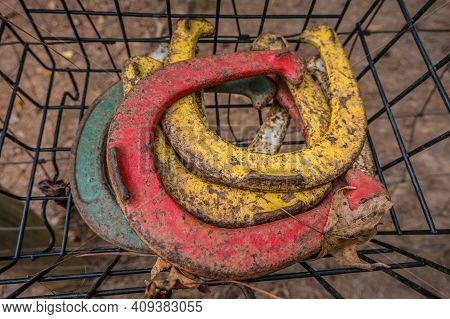 A Collection Of Worn Colorful Iron Horseshoes In A Wire Basket Closeup For Playing A Toss Game Outdo