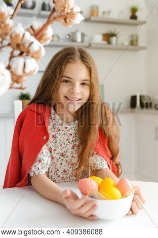 European Girl 10 Years Old Smiles In The Kitchen At The Table With Easter Eggs