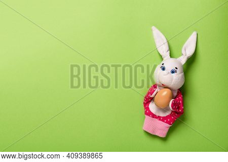Banner with bunny and an Easter egg on pink background with copy space, empty text place. Christian holiday card. Springtime. Toy theater. Online course for painting eggs. Hand puppet. Childhood play.