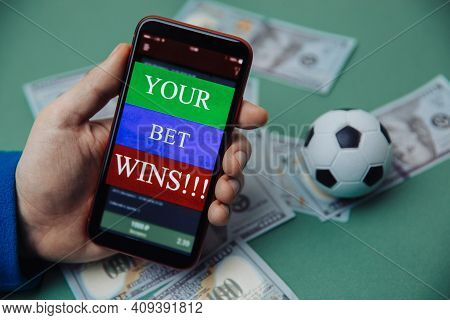 Males Hand Holds Smartphone With Bet Application. Victory Message. Gambling And Bet Concept