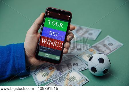 Males Hand Holds Smartphone With Bet Application. Betting Concept