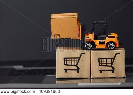 Orange Toy Forklift With Carton Boxes On Keyboard. Logistics And Wholesale Concept