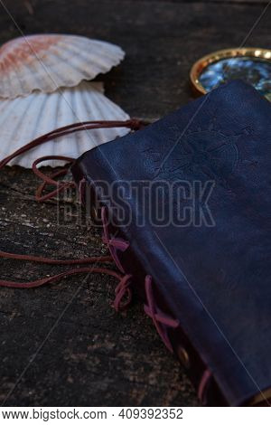 On The Wooden Table Is A Leather-bound Notebook