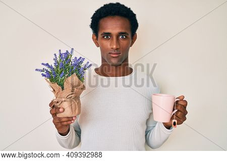 Indian man drinking a cup of infused lavender relaxed with serious expression on face. simple and natural looking at the camera.