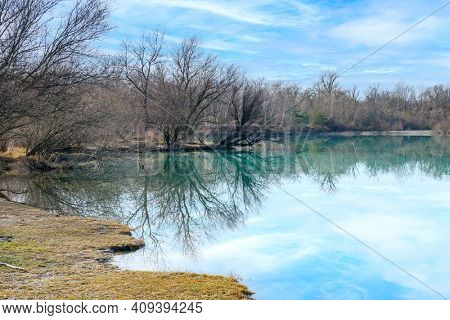 An image of some trees reflections at the lake at a sunny day