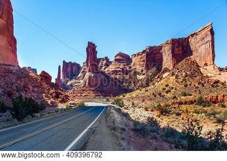 Asphalt road. Picturesque red-brown sandstone cliffs form a unique landscape. The unique beauty of Arches Park. Grandiose rock compositions natural origin. Arches Park in Utah, USA.