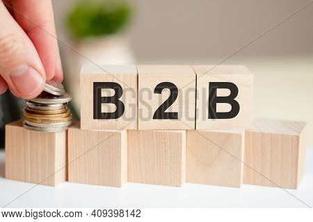 The Word B2b Written On Wood Cubes. A Man's Hand Places The Coins On The Surface Of The Cube. Green