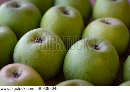 Few Apples Stand On A Wooden Surface