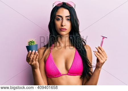 Beautiful hispanic woman wearing bikini holding cactus and razor relaxed with serious expression on face. simple and natural looking at the camera.