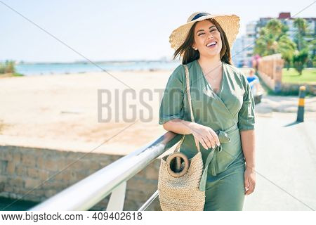 Young hispanic woman on vacation smiling happy leaning on balustrade at the beach