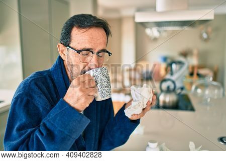 Middle age man feeling sick with cold and fever at home, ill with flu disease drinking a cup of coffee