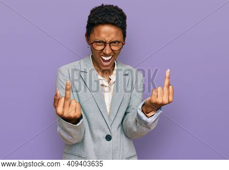 Young african american woman wearing business clothes showing middle finger doing fuck you bad expression, provocation and rude attitude. screaming excited
