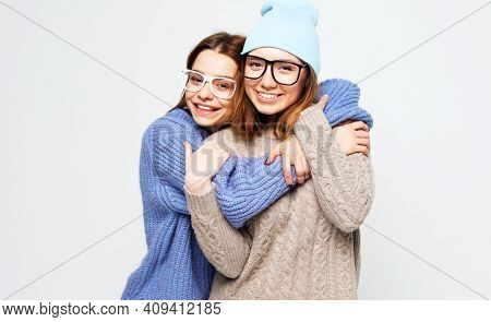 lifestyle, people and friendship concept: Two young female friends standing together
