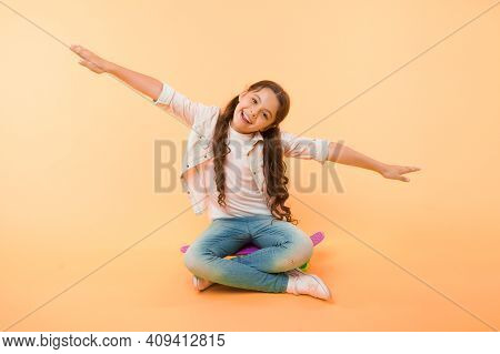 Girl Sit Penny Board Yellow Background. Child Smiling Face Pretend Fly On Skateboard. Kid Relax Sit