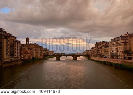 View Of Saint Trinity Bridge And The Arno River From Ponte Vecchio, Surrounded By Picturesque Buildi