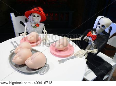 Dressed Up Halloween Skeleton Couple Sitting Down To Dinner Of Plate Of Doll Baby Heads